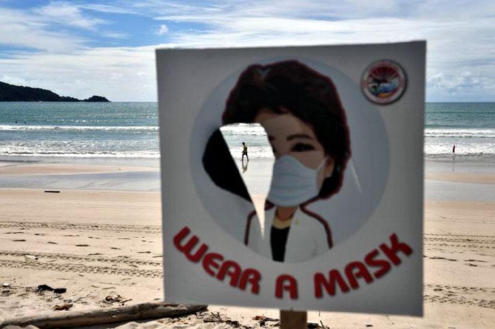 A man walks along the empty beach at Patong, Phuket, seen through a torn sign telling people to wear a mask. (Photo: Lillian Suwanrumpha/AFP)
